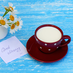 Daisy flowers and cup of milk with good morning note on rustic blue wooden background