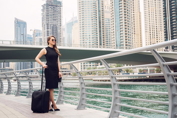 Businesswoman pulling a suitcase in a big city.