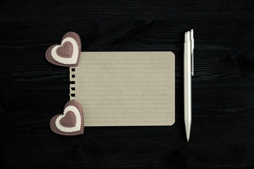 A blank sheet of paper, pen and two hearts on a wooden background. Photo in vintage style