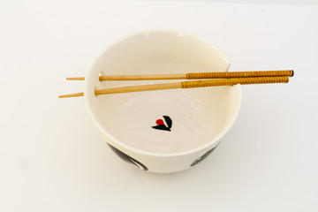 Deep white ceramic bowl with holes for sticks and drawings