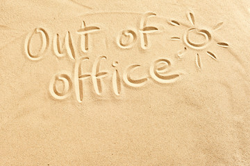 Out of office sign on beach sand
