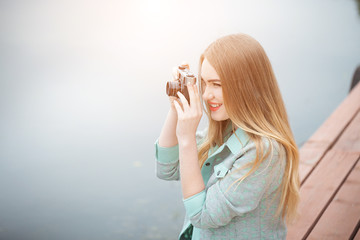 Pretty young woman traveling with photo camera and making pictures