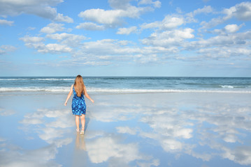 Girl walking toward water enjoying warm summer day on her vacation. Blue sky and ocean in the background. Beautiful clouds and sky reflected on the beach. Jacksonville, Florida, USA.