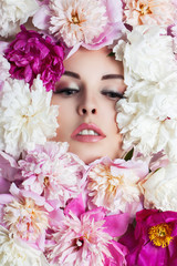 Face of young beautiful woman surrounded by flowers. Peonies closeup.