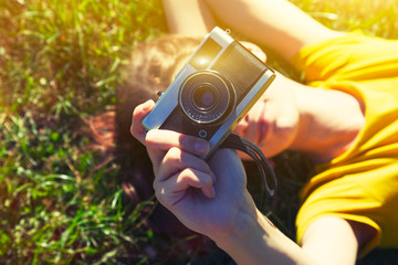 smiling girl lying in grass with film camera