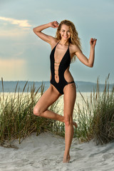 Gorgeous Caucasian girl with slim fit body in black swimsuit enjoying summer time on the beach.