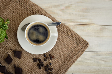 Cup of hot fragrant coffee with beans and chocolate on a mesh fabric.