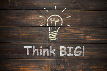 the word think big and light bulb drawn on a wooden board,busine