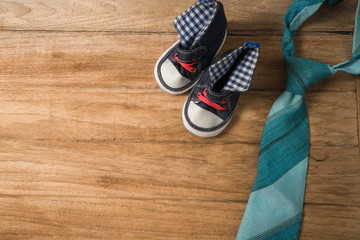 Fathers day composition of colorful tie laid and baby shoes on w