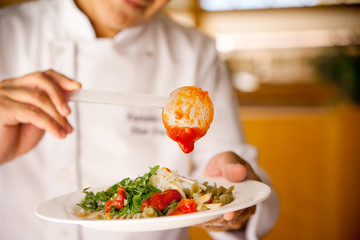 Chef restaurant prepares pasta with parmesan cheese, herbs and tomato sauce waters it