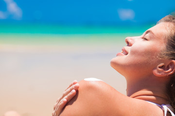 Young woman at beach putting sun cream on shoulder