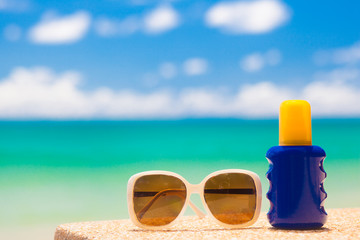 Sunscreen and sunglasses on tropical beach