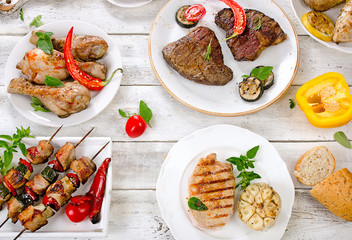 Assorted grilled meats and vegetables on a white wooden table.