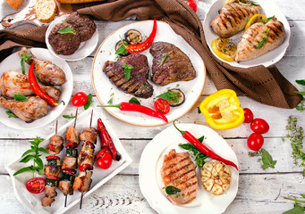 Assorted grilled meats and vegetables on a wooden background.