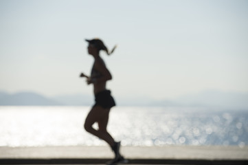 A jogger passes in defocus blur silhouette on the Copacabana boardwalk in Rio de Janeiro, Brazil