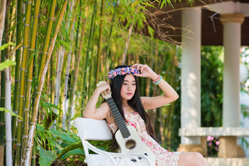girl in a wreath of wild flowers with her guitar