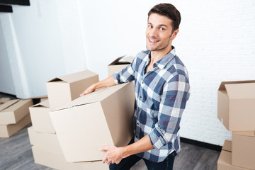 Happy man moving in and carrying carton boxes