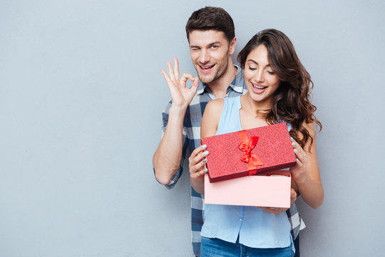 Young woman receiving gift from her boyfriend over gray background
