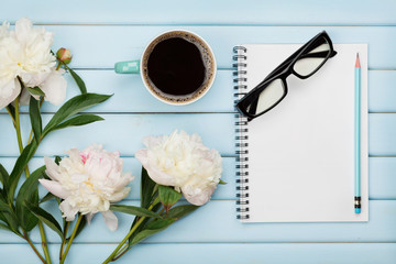 Morning coffee mug, empty notebook, pencil, glasses and white peony flowers on blue wooden table, cozy summer breakfast, top view, flat lay