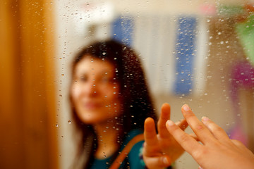 misty reflection of girl in the mirror with water droplets.