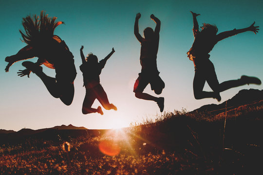 Four people jumping over the sky at sunset. Sunbeam in the background.