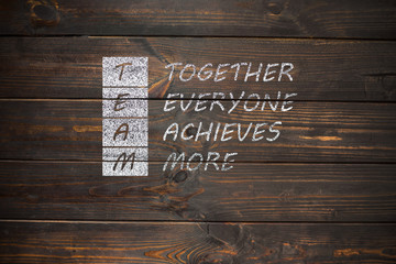 Hand writing TEAM - Together Everyone Achieves More with white c
