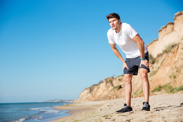 Handsome sportsman standing on the beach