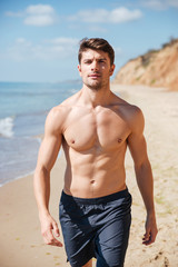Confident shirtless young man walking along the beach