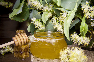 Jar with honey, honeycomb with pollen and linden flowers on a dark wooden background
