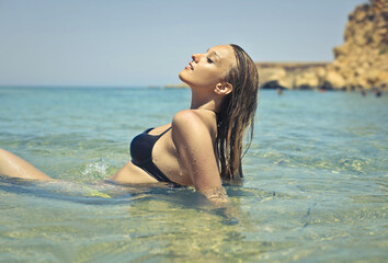 Blonde woman in the water at the seaside