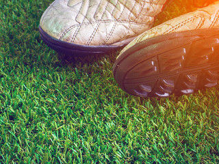 Old muddy dirty football shoes on artificial grass with copy spa