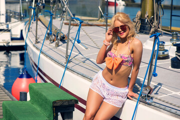 Young beautiful blond woman in color two–piece swimsuit and white transparent shorts on yacht at sunny day