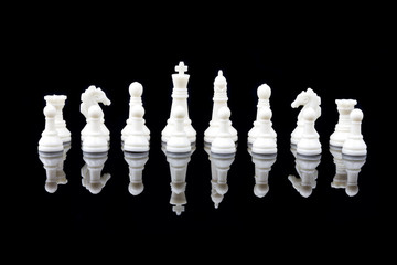 White chess pieces on black background with reflection