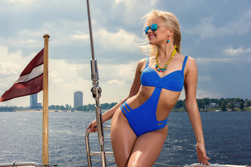 Young beautiful woman in blue one piece swimsuit standing on yacht at sunny day