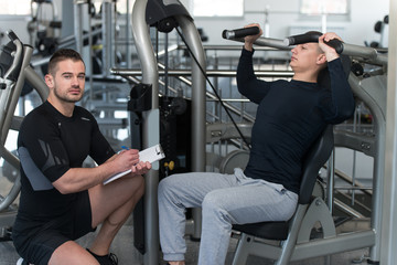 Man Train Shoulders On Machine With Personal Trainer