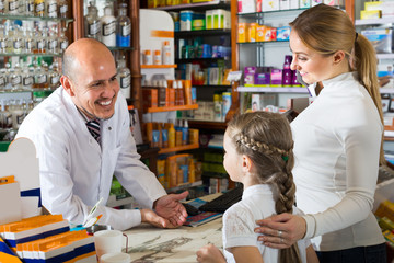 Male pharmacist at the counter in pharmacy .