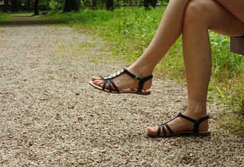 Crossed female legs shod in sandals on the gravel road in the park