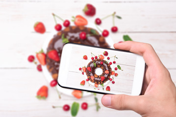 Hands taking photo homemade berry  cake with chocolate with smartphone.