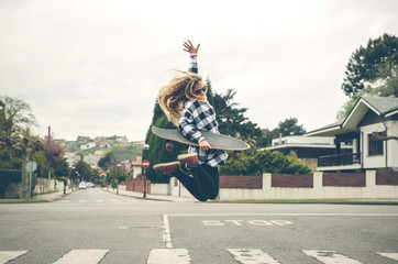 Carefree young woman with skateboard jumping on the street