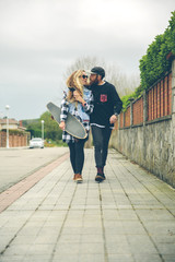 Couple in love with skateboard walking on pavement