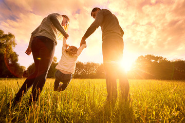 Parents hold the baby's hands. Happy family in the park evening