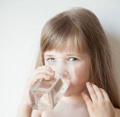 Beautiful little girl drinking water