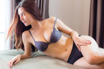 Beautiful women wearing sexy lingerie, standing by the window.