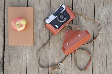 the old camera with the book on a wooden background