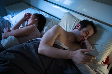 Sly boyfriend using mobile in bed while his girlfriend is sleepi