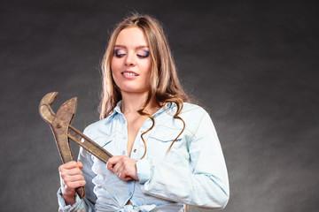 Seductive woman holding monkey wrench. Feminism.