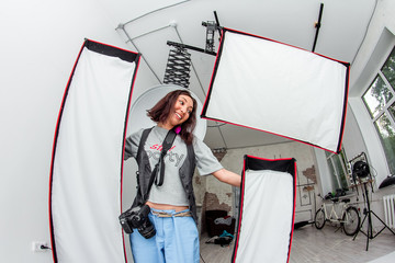 Photographer woman with wide range of different studio lighting