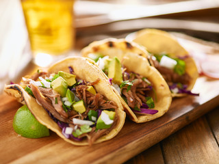 Wall Mural - tasty mexican carnitas tacos with red cabbage, avocado, onion and cilantro