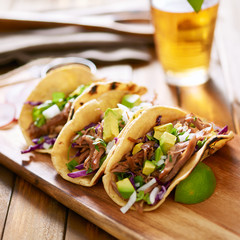 mexican pork carnitas tacos on yellow corn tortilla.