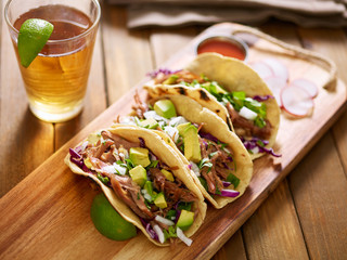 Wall Mural - three  pork carnitas street tacos in yellow corn tortilla with avocado, onion, cilantro and cabbage